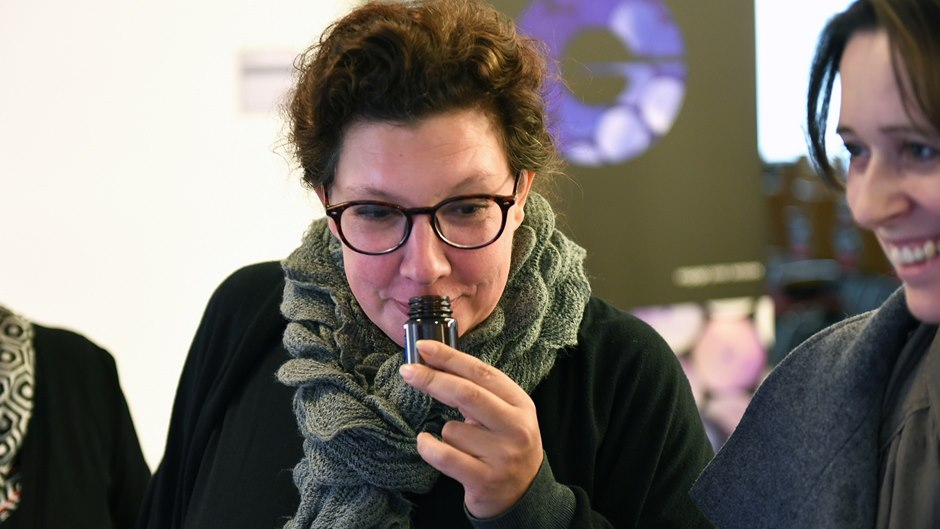 woman smelling on one fragrance bottle