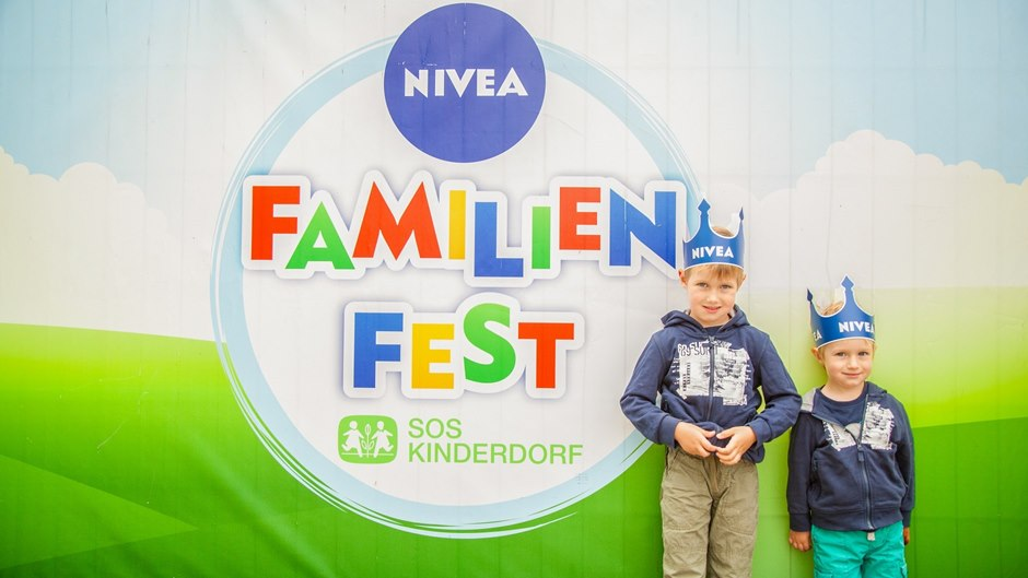 two boys in front of NIVEA family parties poster