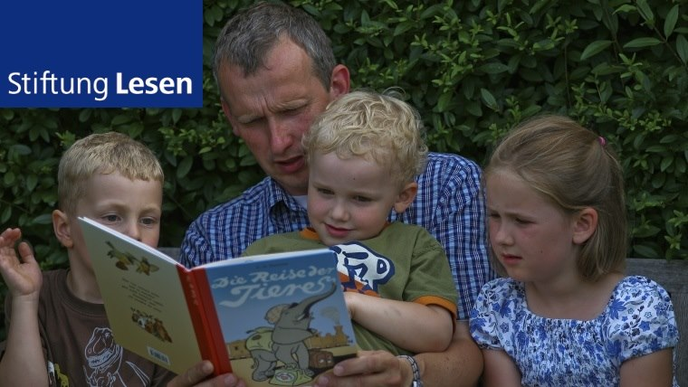 employee of Stiftung Lesen reads out to three children