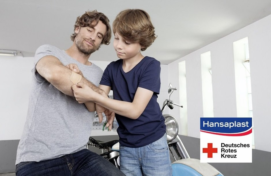 son puts on a plaster on his dad's arm